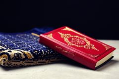 Holy book of Muslims and prayer rug. On table Stock Images