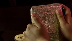 The Holy book of muslims/ Quran hands hold the koran. Hands Holding holy book of muslims on the black background Royalty Free Stock Photos