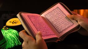 The Holy book of muslims/ Quran hands hold the koran. Hands Holding holy book of muslims on the black background stock image