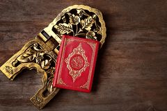 Holy book of Muslims and stand. On wooden background Royalty Free Stock Image