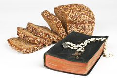 Holy bread. Bread, rosary and bible on white royalty free stock photos