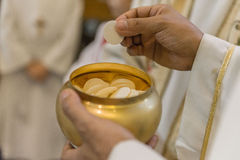 The Holy Bread during the Communion. The christian rite of the Communion during the mass Royalty Free Stock Image