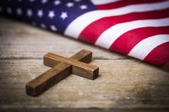 Holy Christian Cross and American Flag Background. A holy wooden Christian cross laying on a wood background with an American flag royalty free stock photos