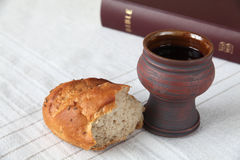Holy communion. Chalice with red wine, bread and Holy Bible on a tablecloth. Shallow dof, copy space royalty free stock image