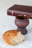 Holy communion. Chalice with red wine, bread and Holy Bible on a tablecloth. Shallow dof, copy space stock image
