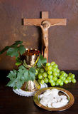Holy communion. Image showing a golden chalice with grapes and bread wafers Stock Image