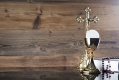 Catholic holidays – Easter. Place for typography and logo. Holy communion. Catholic theme. The Cross, chalice, rosary and Bible  Rustic wooden background Royalty Free Stock Photography