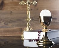 Catholic holidays – Easter. Place for typography and logo. Holy communion. Catholic theme. The Cross, chalice, rosary and Bible  Rustic wooden background Stock Image