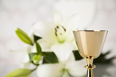 Holy communion a golden chalice with grapes and bread wafers. Eucharist, sacrament of communion background royalty free stock image