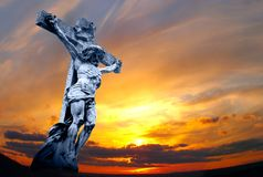 Holy cross with crucified Jesus. Marble holy cross with crucified Jesus Christ against dramatic sunset Stock Images