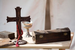 Holy Cross, Goblet and Chest on Table. Stuff from the middle age on a wooden table Royalty Free Stock Image