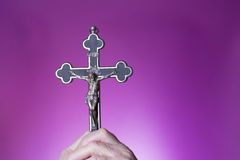 Holy crucifix in hand. On purple background Royalty Free Stock Photos