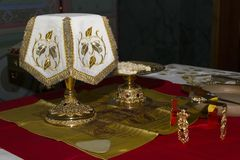 Holy Eucharist in orthodox church. Prepared for sanctification pieces of bread on paten and wine in covered chalice on Holy See, during orthodox liturgy on royalty free stock image