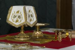 Holy Eucharist in orthodox church. Prepared for sanctification pieces of bread on paten and wine in covered chalice on Holy See, during orthodox liturgy on stock photos