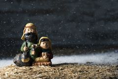 The holy family in a rustic nativity scene. The holy family, the child jesus, the virgin mary and saint joseph, in a simple rustic nativity scene, while snowing royalty free stock photo