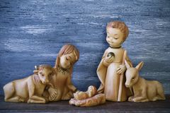 The holy family in a rustic nativity scene. The holy family, the Child Jesus, the Virgin Mary and Saint Joseph, on a wooden surface, against a gray rustic wooden stock images