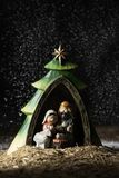 The holy family in a rustic nativity scene. The holy family, the child jesus, the virgin mary and saint joseph, in a simple rustic nativity scene, while snowing stock images