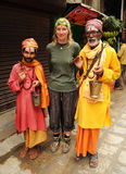 Holy hindu men with blond woman, Nepal. KATHMANDU, NEPAL - OCTOBER 1: Nepalese holy men pose for picture with european tourist on October 1, 2010 in Kathmandu Royalty Free Stock Image