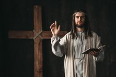 Holy Jesus Christ praying with biblical in hands. Cross on black background. Prayer against crucifixion, christianity symbol stock photos