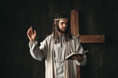 Holy Jesus Christ praying with biblical in hands. Cross on black background. Prayer against crucifixion, christianity symbol stock image