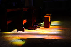 Holy light. Coloured light from a stained glasss window shining on a church pew Stock Image