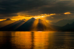 Holy light. The sunlight comin out between from clouds and the pass gently the mountains and reflection to sea stock photo
