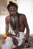 Holy man with bindi and buddhist prayer beads. Holy man with bindi, buddhist prayer beads and loin cloth sitting in front of a buddhist temple in Varanasi, India Stock Photos