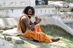 Holy man with flute. A indian man playing a flute Royalty Free Stock Photography