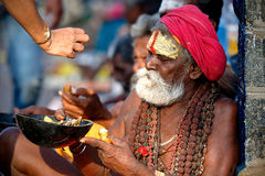 Holy man from India waiting for a charity Royalty Free Stock Photos