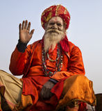 Holy Man lifting hand in greeting, Varanai, India. Varanasi, India- December 27, 2014: Holy Man sitting at the Ghats at Varanasi, the holiest of the seven sacred Royalty Free Stock Images