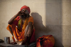 Holy man in orange robes smoking Royalty Free Stock Photos