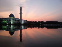 Holy Mosque in kajang view during calm sunrise with reflection at a lake (soft focus, shallow DOF, slight motion blur) Royalty Free Stock Photos