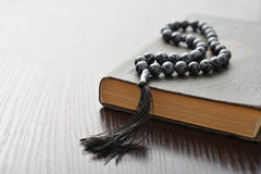 Holy Quran with beads. Over wooden background closeup. Small shallow DOF Royalty Free Stock Photo