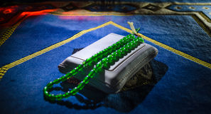 Holy Quran with beads on a prayer mat, Muslim Tasbih is a string of prayer beads which is traditionally used by Muslims along with Stock Image