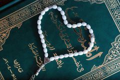 Holy Quran Book With Rosary. Prayer Concept. toned. Green Holy Quran Book with white beads in the shape of a heart on a brown wooden background. Prayer Concept Stock Photography