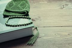 Holy Quran Book With Rosary. Prayer Concept. toned. Greens Holy Quran Book With Rosary on a brown wooden background. Prayer Concept. toned Stock Photo