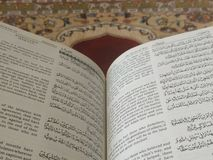 The Holy Quran in English and Arabic on a beautiful Eastern-Pattern Styled Rug stock images