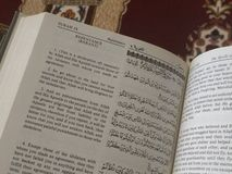 The Holy Quran in English and Arabic on a beautiful Eastern-Pattern Styled Rug stock image