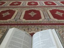 The Holy Quran in English and Arabic on a beautiful Eastern-Pattern Styled Rug royalty free stock images