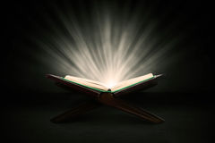 Holy quran with rays. Muslim holy book of koran shot in studio on dark background, with shiny rays Stock Images