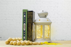 Holy Quran, rosary  and lantern on wooden table, with white bric Stock Image