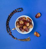Holy Ramadan Fresh Fruits, Dates and Rosary. A Bowel of Ramadan Fresh Fruits, Dates and Rosary, on Blue Background royalty free stock photography