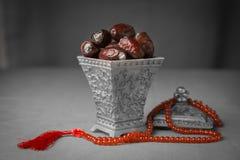 Sacred sweet dates and Islamic praying beads. Stock Image