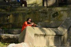 Holy Sadhu man singing on flute in Pashupatinath, Nepal Royalty Free Stock Photo