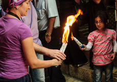 Holy Saturday in Jerusalem. JERUSALEM - APRIL 19, 2014: The holy fire from the holy fire ceremony the Church of the Holy Sepulcher shared between pilgrims along Royalty Free Stock Photo