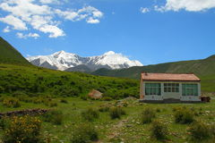 Holy snow mountain Anymachen and Tibetan building on Tibetan Plateau, Qinghai, China.  Royalty Free Stock Image