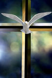Holy Spirit Cross. Beveled glass cross Holy Spirit bird and colorful blurred background Royalty Free Stock Photography
