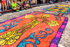 Holy Thursday carpet, Antigua, Guatemala. Antigua, Guatemala - March 24, 2016: Locals admire handmade dyed sawdust Holy Thursday carpets for procession in royalty free stock photo