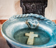 Holy water vestibule-Blue dish with water and cross-Religion Stock Photography