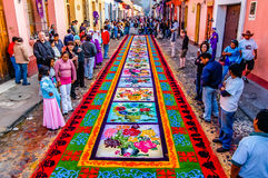 Holy Week carpet, Antigua, Guatemala. Antigua, Guatemala - April 10, 2009: Spectators admire Holy Week carpet on Good Friday morning in Spanish colonial town & stock photography